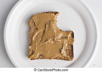 Peanut butter on bread with a bite