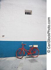 Red bicycle on a white wall background