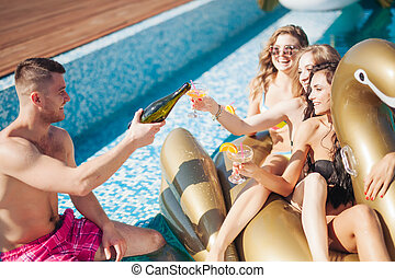 Group Of Friends Having Party In Pool Drinking Champagne. 20s