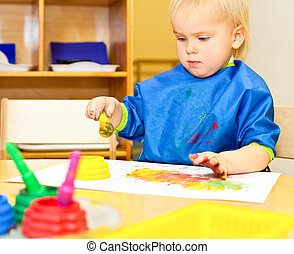 Child at painting lesson - Little girl wearing blue apron...