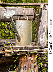watering pot on lod wooden background - old watering pot on...