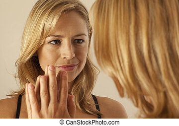 Woman touching mirror while looking at reflection