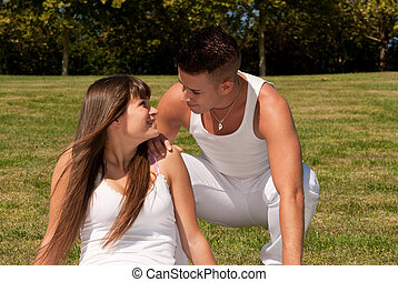 young couple happy sitting on grass white clothes, love...