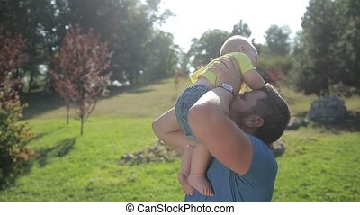 Happy father playing with child raising him up -...