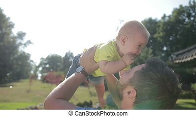 Affectionate young father lifting cute baby boy up -...