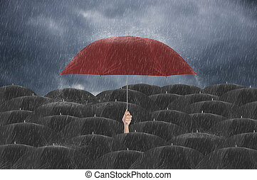 Hand holding red umbrella different among black umbrella. insurance policy Life health protection a family concept.