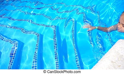 Pretty little girl swimming in outdoor pool and have a fun...