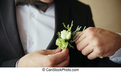 Groom takes wedding boutonniere to suit, close up