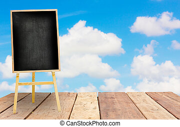 menu black board on old vintage planked wood table in perspective in front of blurred  bright cloudy sky, can be used for display or montage your products. Mock up for displaying product.