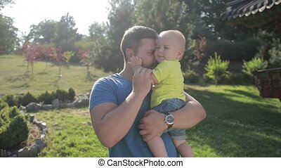 Young hipster father holding little son in park - Smiling...