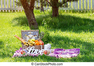 Picnic setting for a couple in love. Carpet with picnic basket in the garden, word LOVE on the grass.