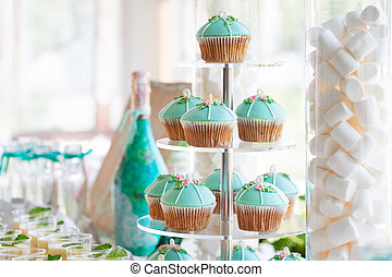 Wedding cupcake tower stand with turquoise cakes.