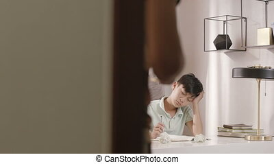 Asian father walking into reading room talking to son frustrated with homework