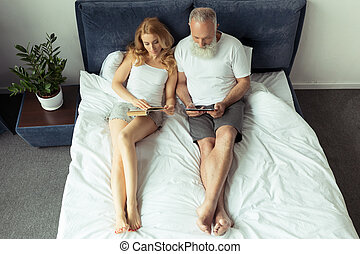 mature couple reading book and using digital tablet while...