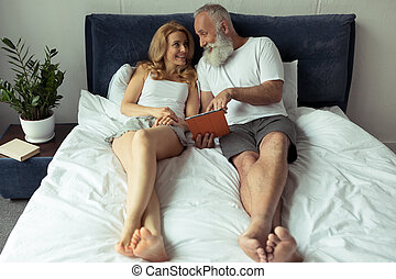 mature couple using digital tablet while lying on bed at...