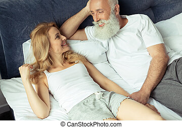 happy mature couple relaxing on bed and looking at each...