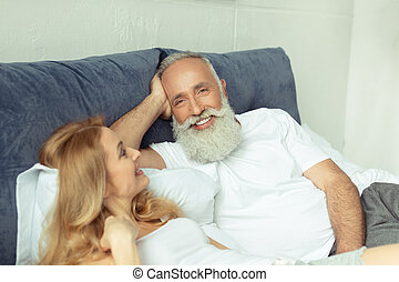 happy mature couple relaxing on bed and looking at camera at...