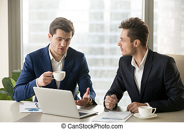 Two businessmen talking, sitting at office desk with laptop...