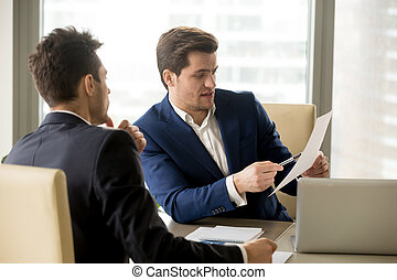 Two serious business partners discussing document, businessmen n