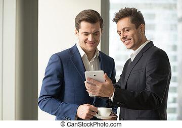 Smiling businessman holding digital tablet showing something...