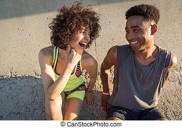 Young happy fitness couple in sportswear talking while...