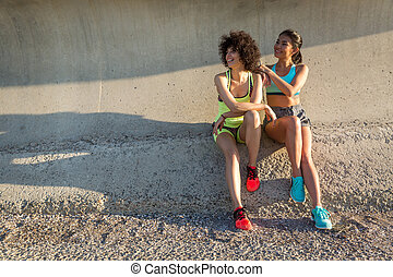 Two happy sporty women in sportswear sitting together while...