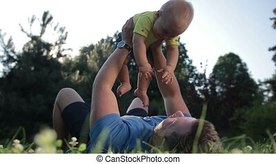 Carefree father holding cute baby son up outdoors - Joyful...
