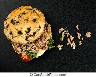 Tuna Nicoise Salad In a Focaccia Bread Bun Against a Black...