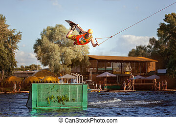 Man jumps over a springboard on the water. - Male...
