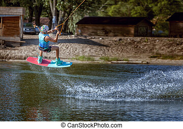 Jump over the water on a wakeboard. - Jump over the water on...