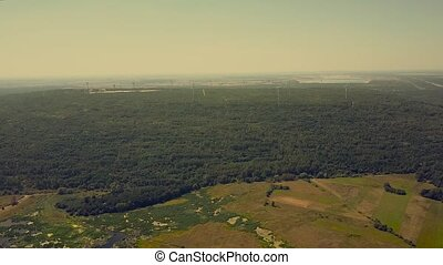 Aerial time lapse of windmills in forest area. Green energy production concept