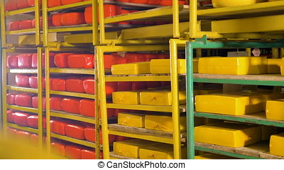 Full storage racks holding yellow and red cheese loaves. -...
