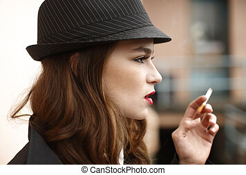 Young and stylish woman smoking a cigarette.