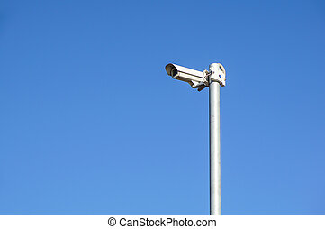 CCTV security camera and surveillance on a pole against the backdrop of blue sky
