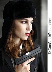 Woman holding a pistol safely with her finger off the...