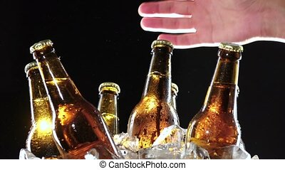 Hand takes a bottle of cold beer. Black background . Close...