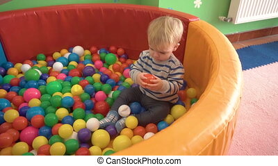 mother playing with her baby boy in room with colourful blocks, balls, kitchen
