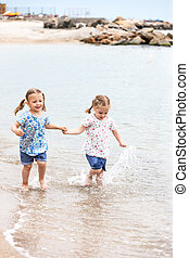Children on the sea beach. Twins going along sea water. -...