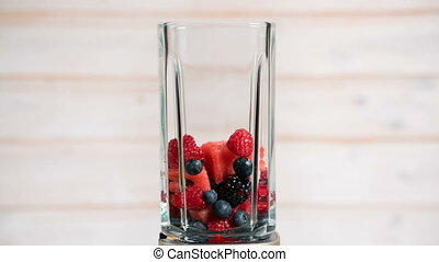 berries appear in a blender and then crushed in smoothie,...