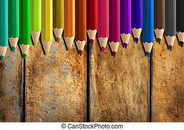 misaligned coloured pencils on wooden desk background - Set...