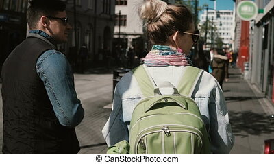 Back view of young tourists couple walking in city centre...