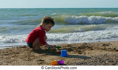 Little boy is playing on the beach in the sand and boasting