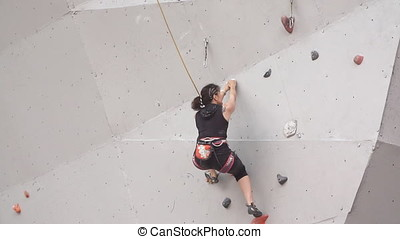 girl mountaineer with climbing equipments. slow motion....