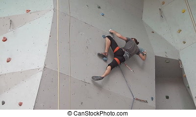 Amateur extreme relaxation training in mountaineering. young athletic guy climbs on the rock on the climbing wall. slow motion.