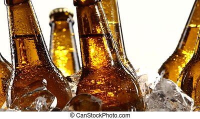 Dark bottles twist in pieces of clear ice. White background....