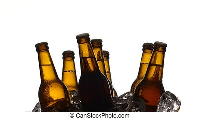 Bottles of dark cold beer in the ice. White background....