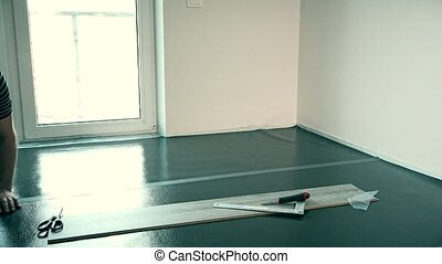 male builder taping down flooring underlay with tape. Static...
