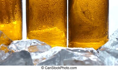 Ice lies on the table, behind it are bottles of beer. White...