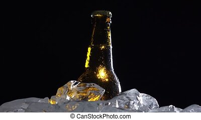 Bottle of dark cold beer in the ice. Black background....