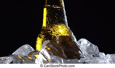 Condensate flows down the brown glass of bottle from beer....